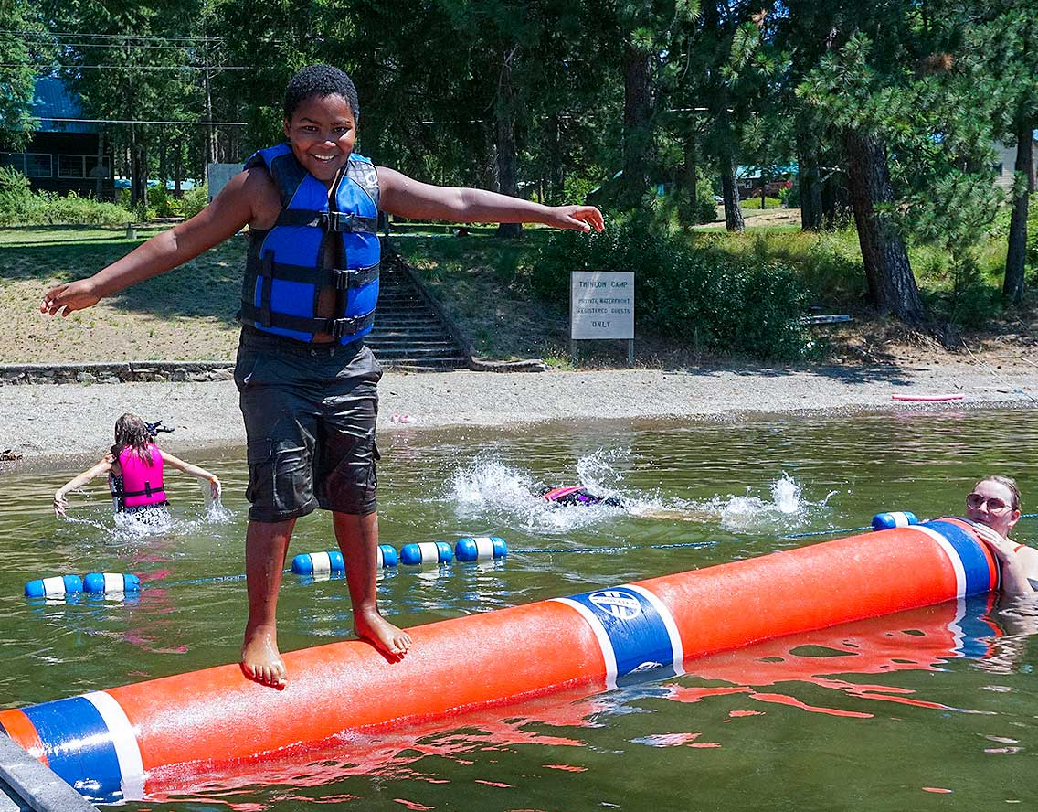 kid on log rolling in lake