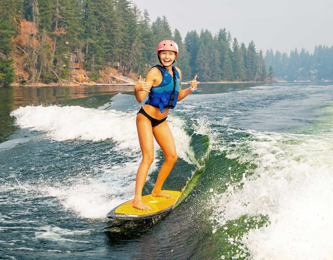 High school campera surfing behind Supra Wakeboard Boat